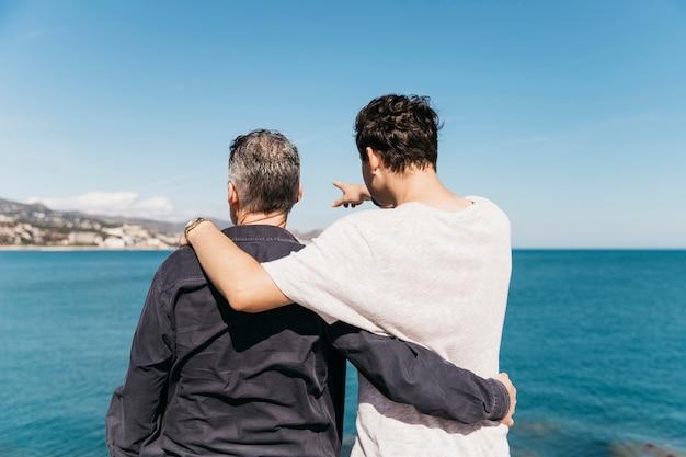 Concetto di giorno di padri con padre e figlio di fronte al mare