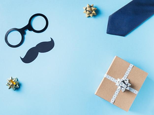 Concetto di giorno di padri con scatola regalo, cravatta e baffi su sfondo blu