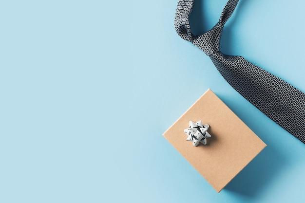 Concetto di giorno di padri con scatola regalo e cravatta su sfondo blu