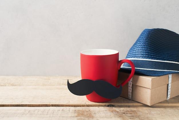 Concetto di giorno di padri con tazza rossa e baffi e regalo, cravatta su sfondo bianco
