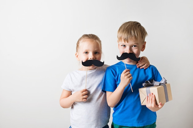 Concetto di giorno di padri, due piccoli bambini caucasici che sorridono con i baffi su fondo bianco
