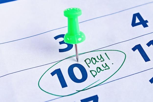 Concetto di giorno di paga. affari, finanza, risparmi. calendario con il cerchio dell'indicatore nella parola giorno di paga