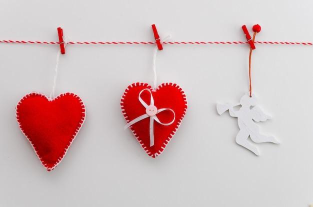 Concetto di giorno di san valentino. cuori di feltro rosso e angelo su corda con molletta.