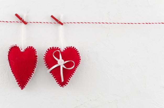 Concetto di giorno di san valentino. due cuori di feltro su corda con molletta.
