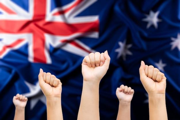 Concetto di giorno in australia. mani di persone con bandiera australiana in background.