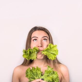 Concetto di giovane donna che mangia insalata fresca