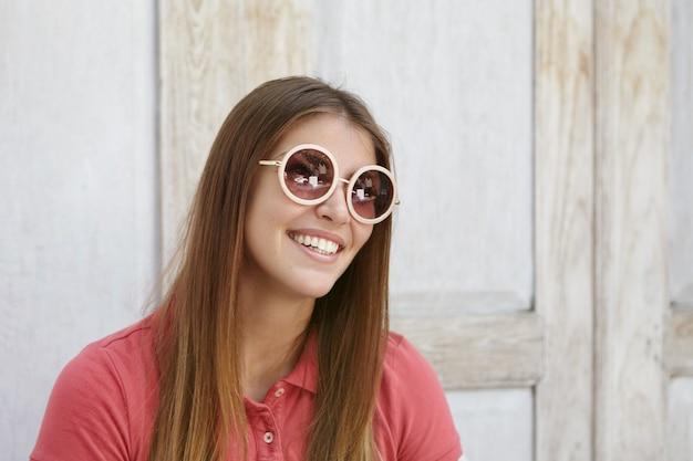 Concetto di gioventù e felicità. tiro al coperto di giovane donna alla moda con taglio di capelli lungo che indossa sfumature rotonde sorridenti e divertirsi alla parete di legno