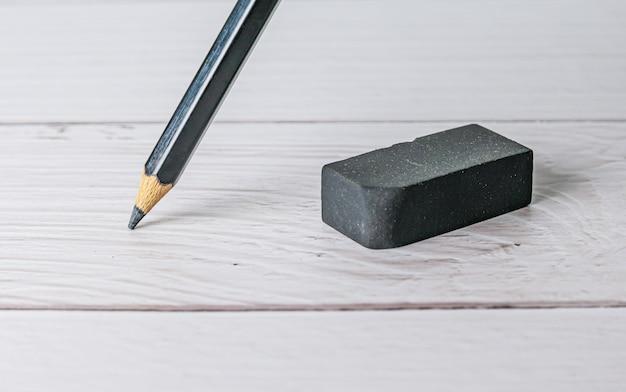 Concetto di gomma ed errore, gomma e matita sulla tavola bianca