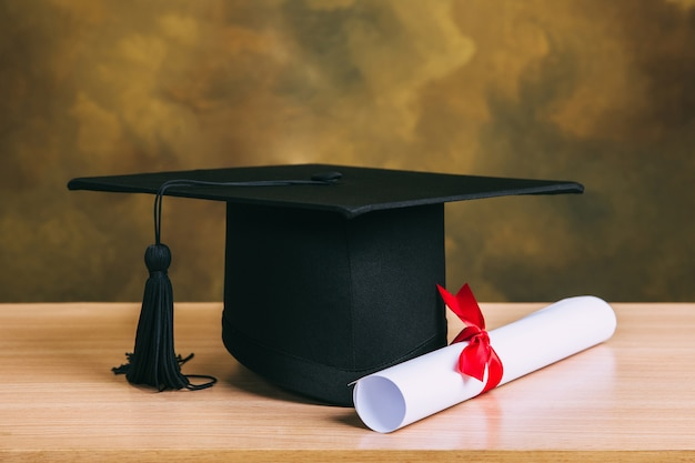 Concetto di graduazione. tappo di laurea, cappello con carta di laurea sul tavolo di legno.