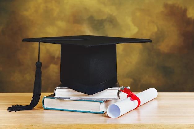 Concetto di graduazione. tappo di laurea, libri con carta di laurea sul tavolo di legno