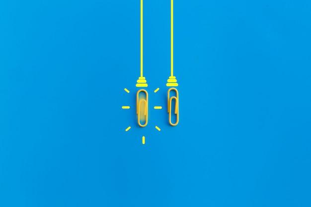 Concetto di grandi idee con graffetta, pensiero, creatività, lampadina su fondo blu, nuovo concetto di idee.