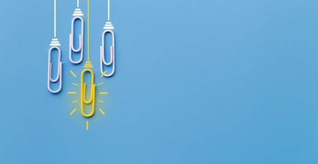 Concetto di grandi idee con graffetta, pensiero, creatività, lampadina su sfondo blu.
