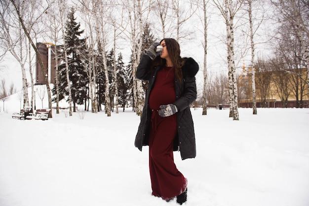 Concetto di gravidanza, bevande, inverno, persone e aspettative