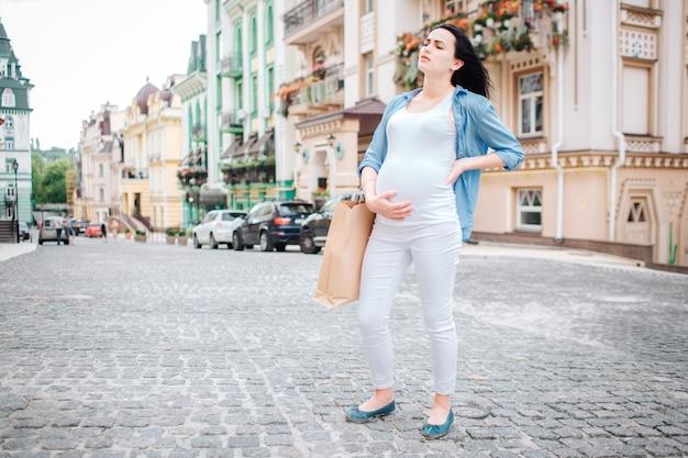 Concetto di gravidanza, di maternità, della gente e di aspettativa - vicino su della donna incinta con i sacchetti della spesa alla via della città. non si sente bene, ha mal di stomaco e alla schiena.