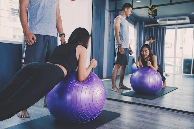 Concetto di gruppo di yoga; giovane che insegna alla donna che pratica yoga in classe; sentirsi tranquilli e rilassarsi nella lezione di yoga