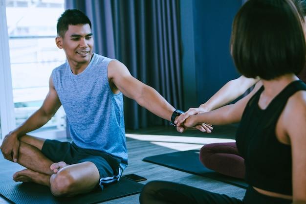Concetto di gruppo di yoga; giovani che praticano yoga in classe; sentirsi tranquilli e rilassarsi nella lezione di yoga