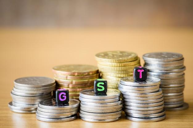 Concetto di gst con blocco alfabeto su un oro impilati di monete.