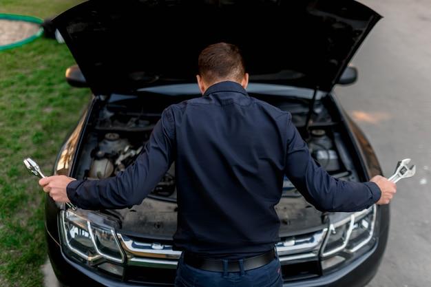 Concetto di guasto dell'auto. l'auto non parte. il giovane sta cercando di sistemare tutto da solo. non possono riparare la macchina da soli. l'assicurazione deve coprire tutti i costi.