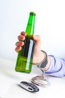 Concetto di guida ubriaca - birra, chiavi e manette