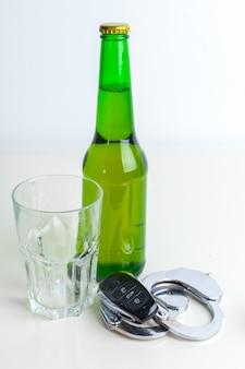 Concetto di guida ubriaco - birra, chiavi e manette