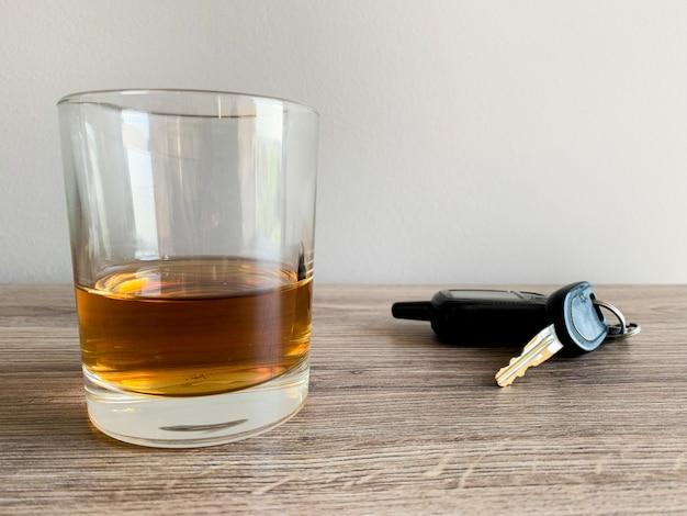 Concetto di guida ubriaco. vetro con whisky e chiave sul tavolo.