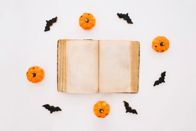 Concetto di halloween con libro, pipistrelli e zucche