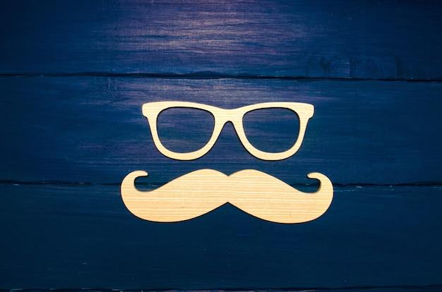 Concetto di hipster. baffi di legno e vetri di legno su una priorità bassa blu
