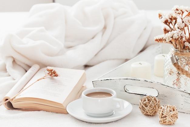 Concetto di hygge scandinavo caldo e accogliente - tazza di caffè con latte e libro aperto.