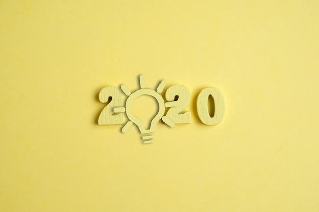 Concetto di idea creativa nel nuovo anno 2020. una lampadina gialla accanto ai numeri sullo sfondo giallo.