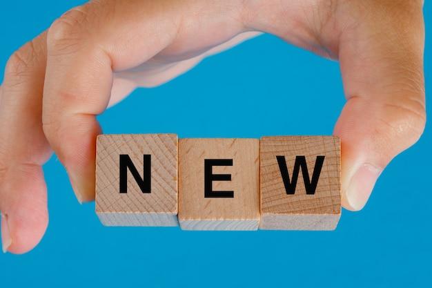 Concetto di idea di affari sulla vista laterale della tavola blu. mano che tiene i cubi di legno con la parola nuova.