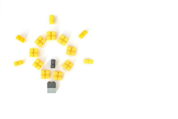 Concetto di idea lampada realizzata con mattoni di costruzione in plastica gialla. giocattoli popolari. copyspace