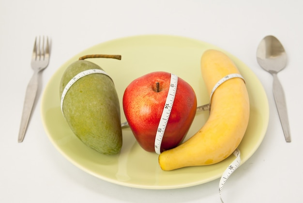 Concetto di iet. frutta e vitamine con metro a nastro su un piatto