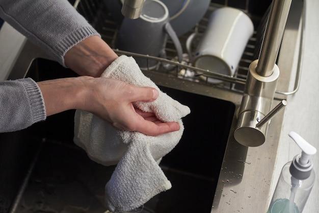 Concetto di igiene, la donna di vista superiore si lava le mani nel lavandino di cucina e si pulisce le mani con l'asciugamano, fuoco selettivo