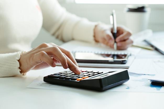 Concetto di imposta la mano della donna facendo uso del calcolatore e della scrittura prende nota con calcola circa l'ufficio di costo a casa lavoro da casa