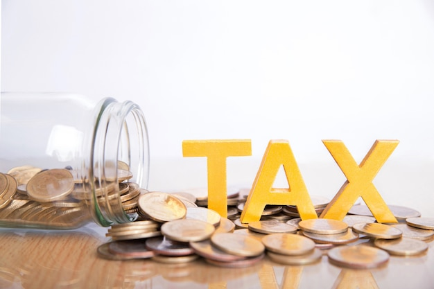 Concetto di imposta. la tassa di parola ha messo sopra le monete e le bottiglie di vetro con le monete dentro su fondo bianco.