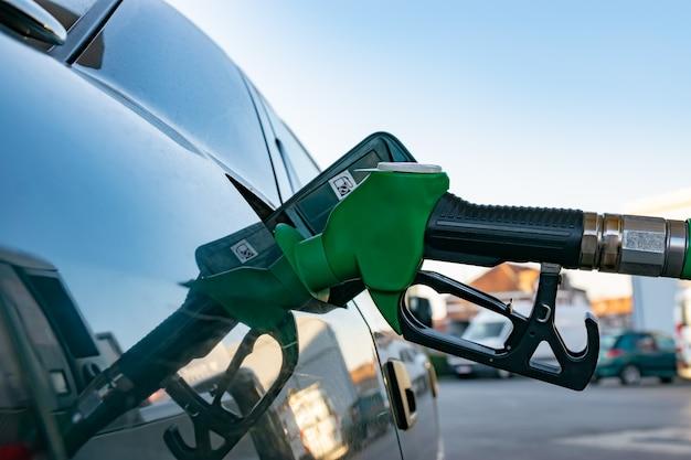 Concetto di industria, oli e combustibili: rifornimento di carburante in una stazione di benzina.