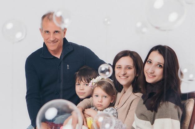 Concetto di infanzia felice, famiglia, amore - gruppo di persone su uno sfondo bianco: adulti e bambini con giocattoli seduti sullo stesso divano