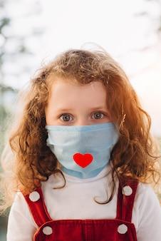 Concetto di infermiera. il ritratto verticale della bambina prescolare che si siede sul davanzale della finestra a casa, indossando la maschera del virus con cuore rosso, esamina la macchina fotografica. epidemia di pandemia che diffonde coronavirus 2019-ncov.