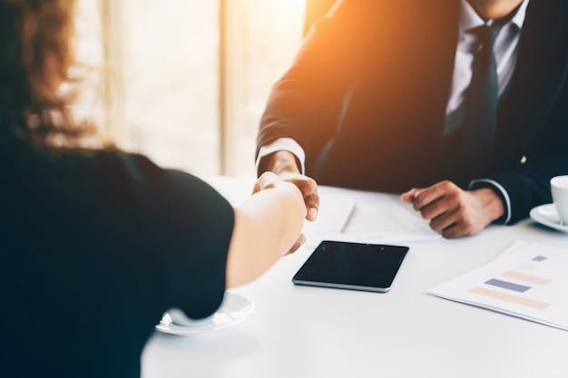 Concetto di intervista di affari - uomo d'affari e donna che fanno stretta di mano in ufficio