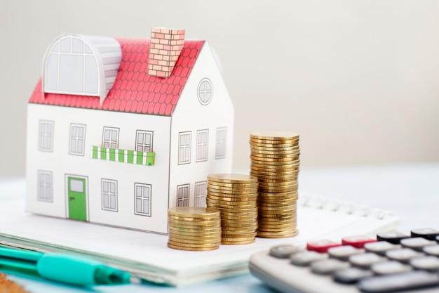 Concetto di investimento del bene immobile, monete dei soldi che crescono e casa miniatura sullo scrittorio.