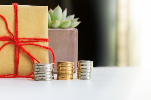 Concetto di investimento e interesse, risparmio di denaro con scatola regalo e piccolo albero
