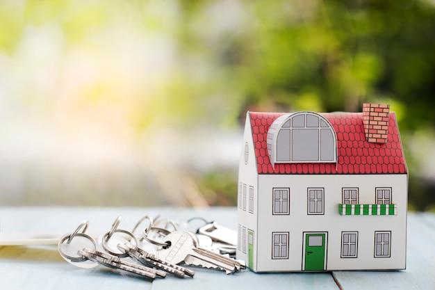 Concetto di investimento immobiliare, casa in miniatura e chiave sulla scrivania.