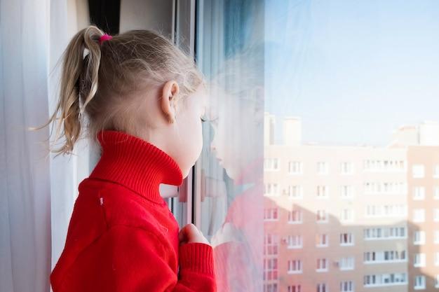 Concetto di isolamento. rimani a casa in quarantena. piccola ragazza triste che guarda fuori dalla finestra. isolamento sociale durante la pandemia covid-19.