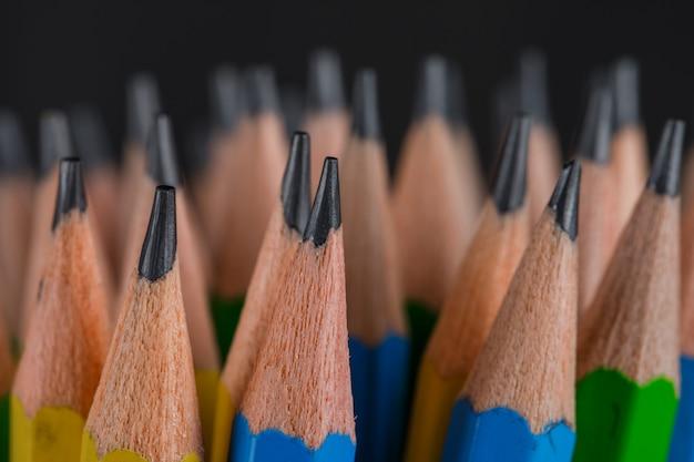 Concetto di istruzione con le matite sul primo piano scuro.