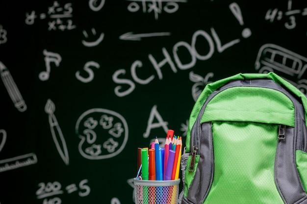 Concetto di istruzione - zaino, taccuini e rifornimenti di scuola verdi da una lavagna