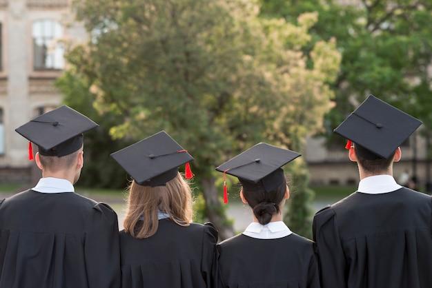 Concetto di laurea con gli studenti da dietro