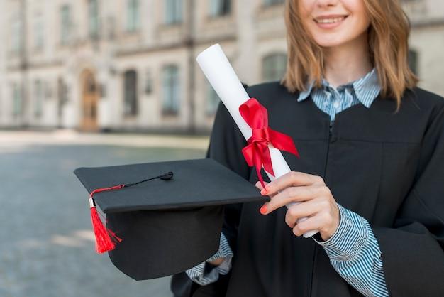 Concetto di laurea con ragazza che tiene il suo diploma
