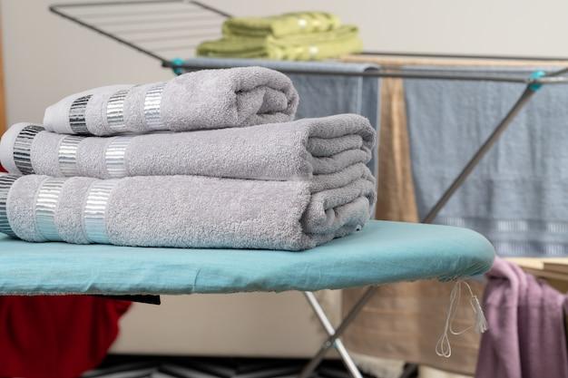 Concetto di lavori domestici. asciugamani da stiro su asse da stiro