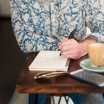 Concetto di lavoro di realxation della caffetteria di scrittura dell'uomo senior