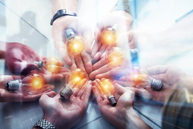 Concetto di lavoro di squadra e di brainstorming con uomini d'affari che condividono un'idea con una lampada. avvio di concept company. esposizione doppia